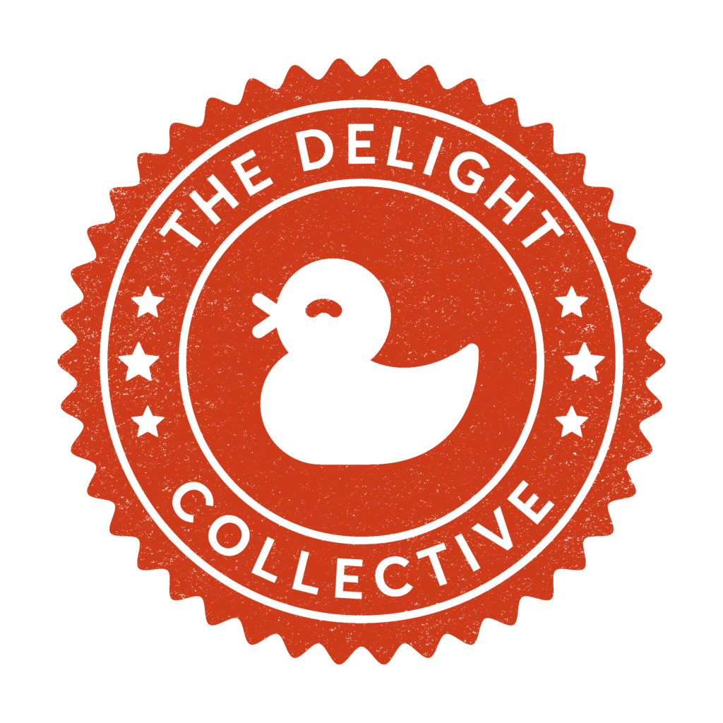 The Delight Collective logo- a white rubber duck in the middle of a red circular stamp